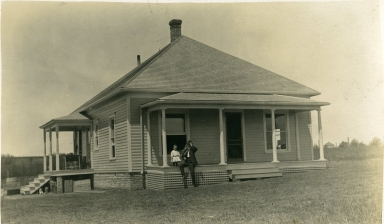 One-story, white frame house with people sitting on porch in Paducah (KY)