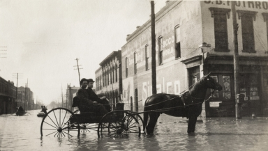 Two men in horse-drawn buggy and two row boats during April 1913 flood in Paducah (KY)