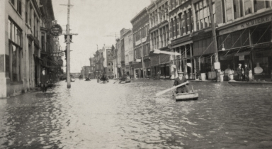 View of flooded Paducah (KY) street with people in boats during April 1913 flood, W M Rieke building to right