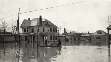 People in boat by house in Paducah (KY) during April 1913 flood