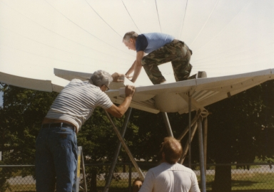 Chief engineer Bill Parmley and engineer Jay Thweatt during satellite installation