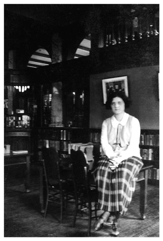 (Untitled) [Woman sitting on table with plaid skirt]