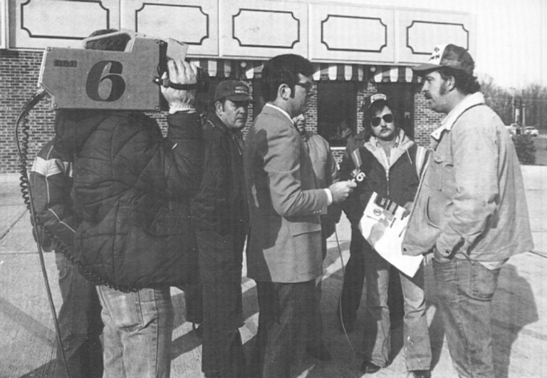 Reporter Ernie Mitchell conducting interview